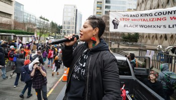 Black-presenting individual (Nikkita Oliver) speaks into microphone in front of protest sign