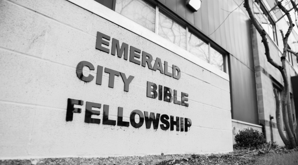 "Black and white photograph of a sign outside a building that says ""Emerald City Bible Fellowship"""