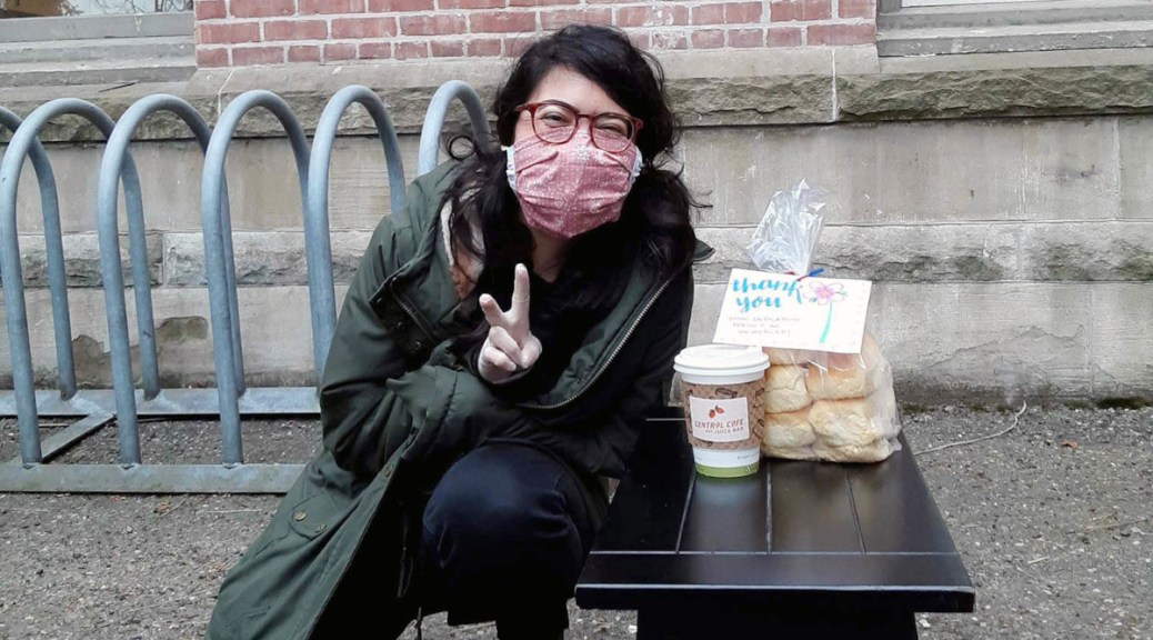 "Masked and bespectacled female-presenting individual sits with coffee, bagels, and a ""Thank You"" note, forming a peace sign with her hand"