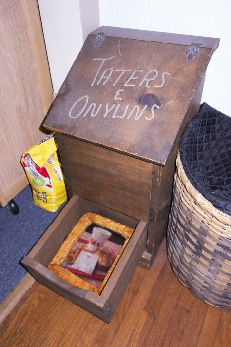 """Photo of a blessing box inscribed with the words """"Taters & Onyuns,"""" a drawer is opened with a framed photo of a tray of fast food from a burger joint."""