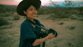 Vivian Hua posing with a camera in Joshua Tree, California.