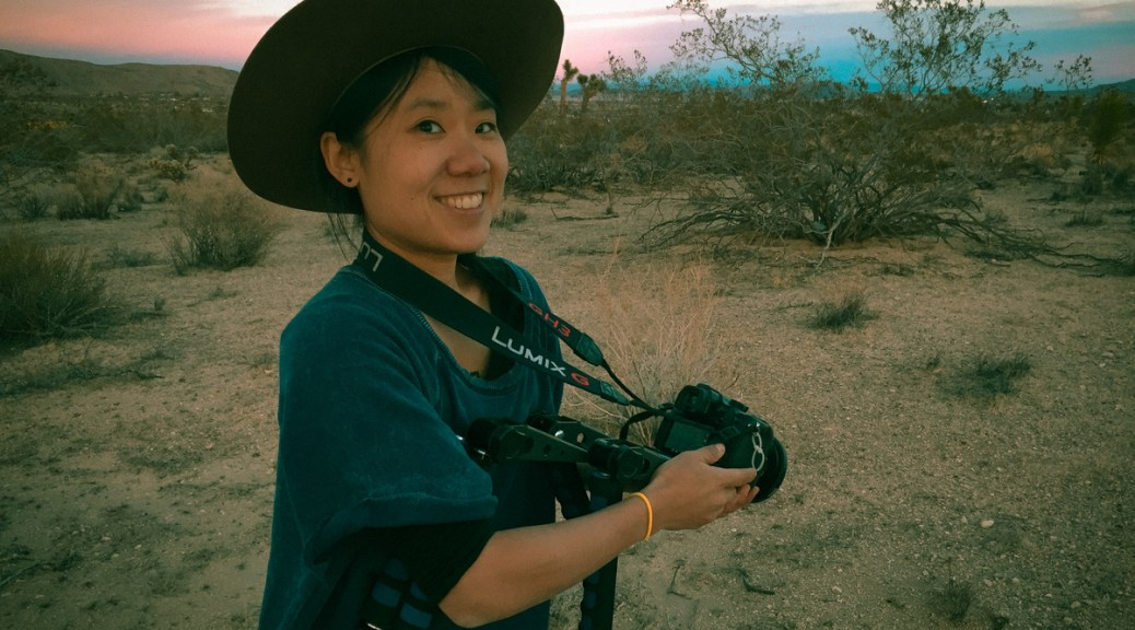 Vivian Hua posing with a camera in Joshua Tree, California.