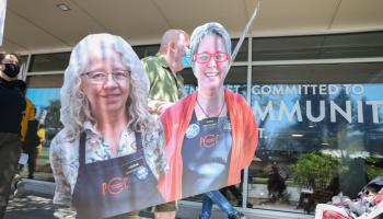 A demonstrator carries a cutout of Donna Rasmussen and Laurae McIntyre during an Apr. 14, 2021 protest at the Columbia City PCC.