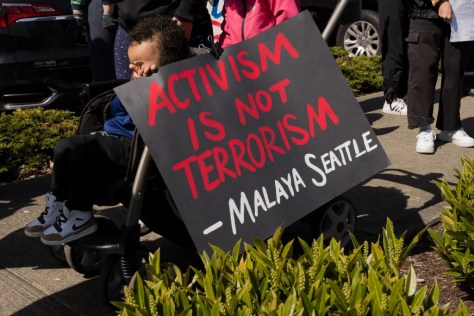 "A young child holds a sign during the rally that reads ""Activism is not Terrorism - Malaya Seattle"""