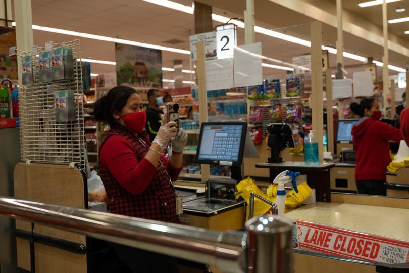 A Seafood City cashier pauses during her shift to record the group of Filipino American activists chanting and marching their way out of the building.