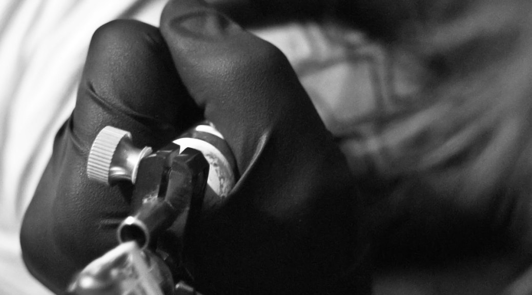 Black and white photo of a gloved hand holding a tattooing device over skin
