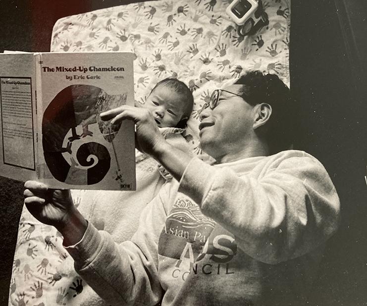 Black and white photo of Bob Shimabukuro reading to his child.