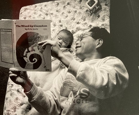 Black and white photo of Bob Shimabukuro reading to his child.