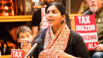 Kshama Sawant speaks at podium with people in the background holding Tax Amazon signs.