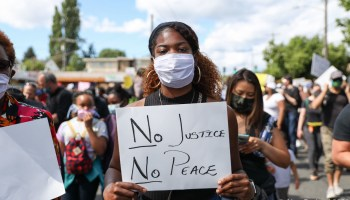 """Protestor holds sign that reads """"No Justice, No Peace"""" in Othello Park."""