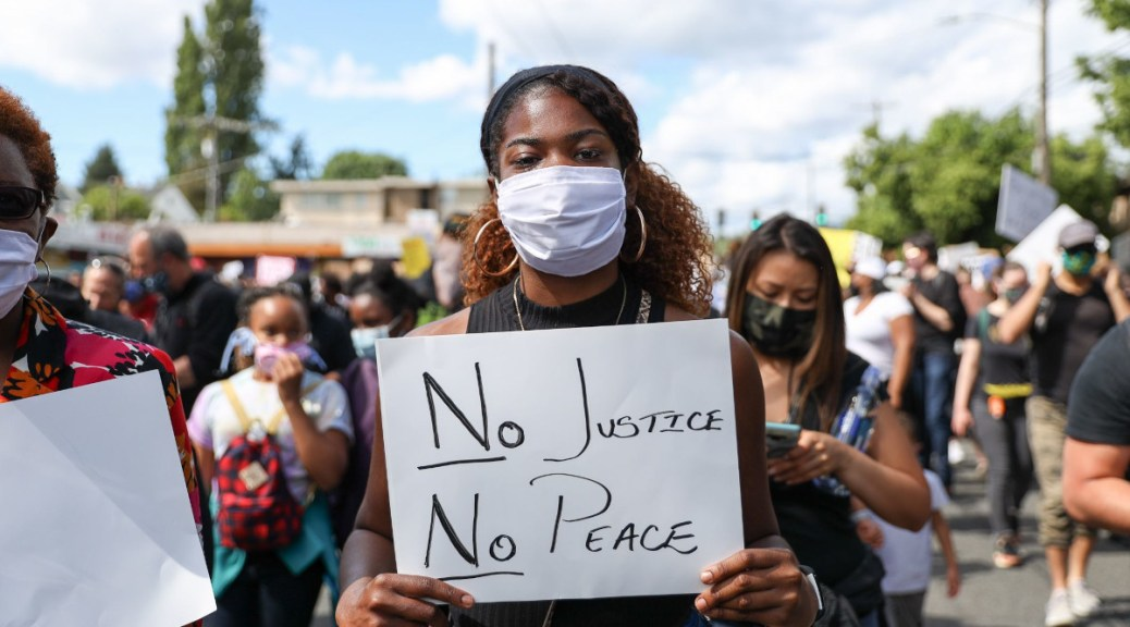 "Protestor holds sign that reads ""No Justice, No Peace"" in Othello Park."