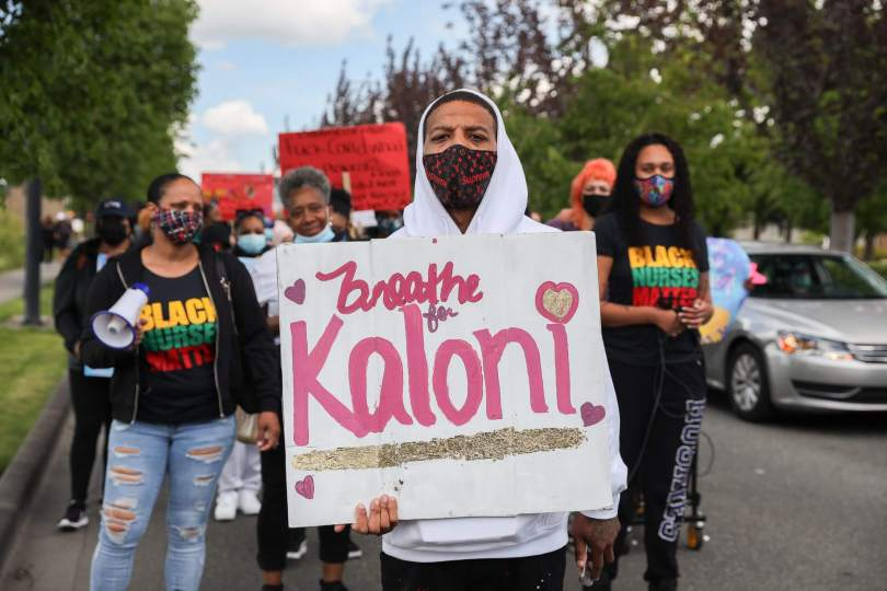 """Marcher carries a sign with pink text that reads """"Breathe for Kaloni."""""""