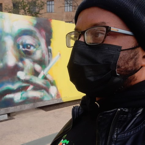 Tyrone Brown photographed in front of a mural of James Baldwin.