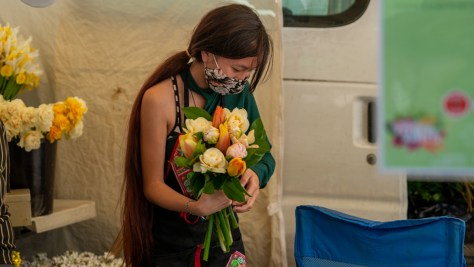 Flower vendor at the Columbia City Farmers Market gathers together fresh flowers into a bouquet.