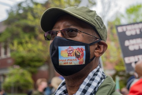 """Local writer and activist Bereket Kiros wears a mask reading """"Tigrians cannot be subdued by force"""" at the 2021 May Day rally."""