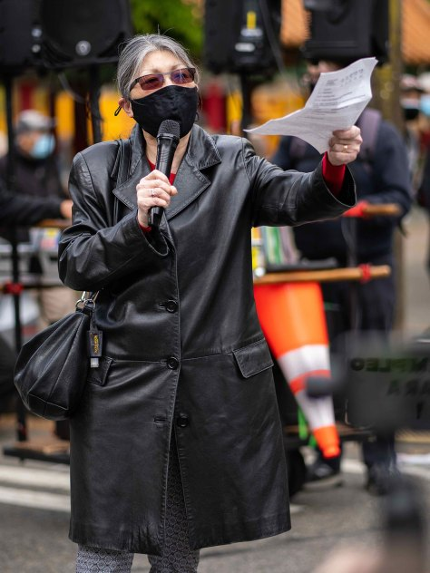 A masked Washington State Rep. Sharon Tomiko Santos speaks by Hing Hay Park, holding a microphone in one hand and paper in the other.