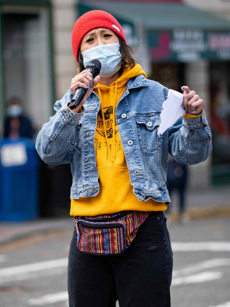 A masked JM Wong, organizer with the Massage Parlor Outreach Project, speaks to the importance of being in solidarity with local Asian immigrant massage workers, holding a microphone in one hand and notebook paper in the other.