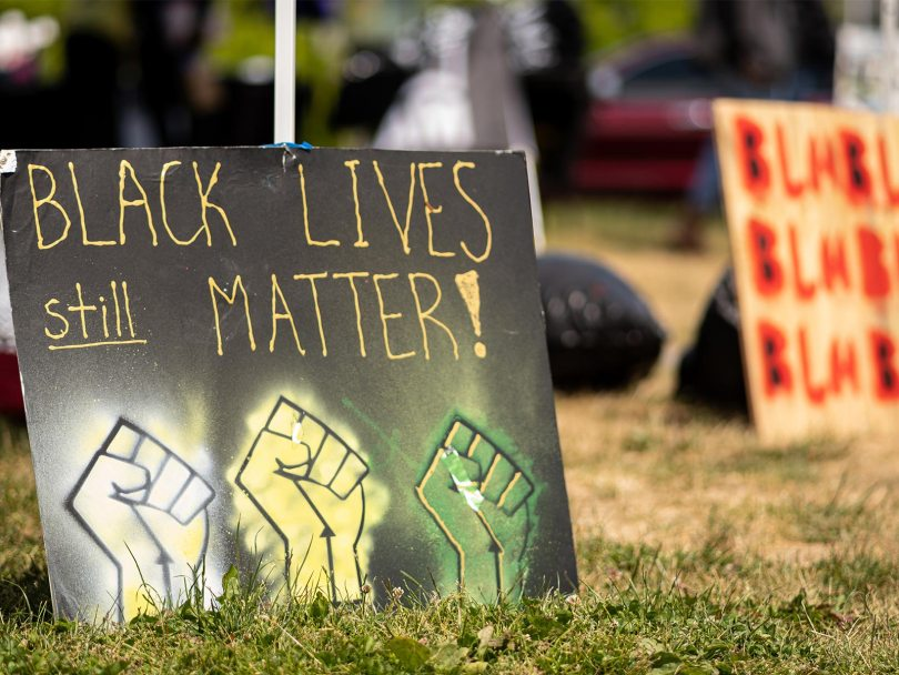 """Black sign on display with yellow text that reads """"Black Lives STILL matter"""" with white, yellow, and green fists."""
