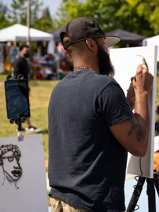 """Local artist LeShawn """"Olodumare"""" Gamble begins his live painting of Malcolm X during the event."""
