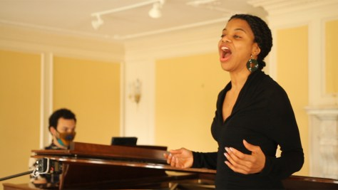 Photo of Ellaina Lewis singing in front of a piano.