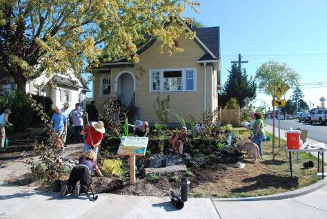 photo of people doing landscape work in front of a house