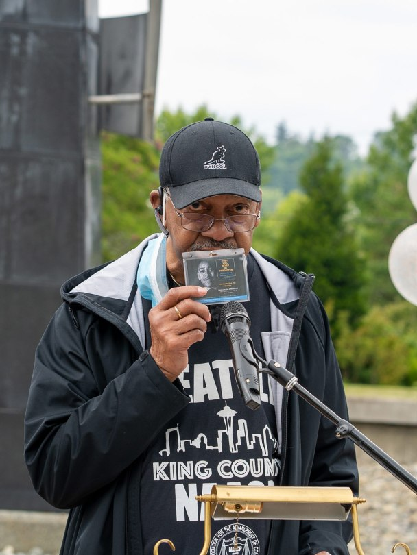 Photo of Seattle King County NAACP Vice President Claude Burfect holding up a badge with a photograph of Emmett Till on it.