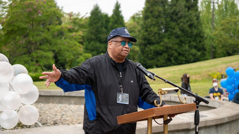 Photo of former King County Councilmember and longtime civil rights leader Larry Gossett giving a brief history of police killings in Seattle at a podium in Martin Luther King Jr. Memorial Park.