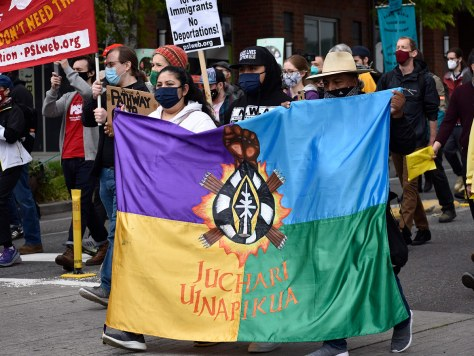 Protesters carry the official flag of the Indigenous Purépecha people as they march down South Jackson Street.