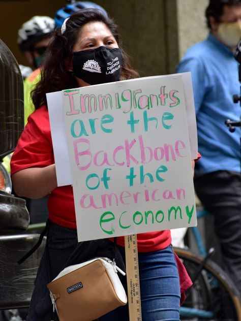 """Protester carries a sign that reads, """"Immigrants are the backbone of the American economy."""""""