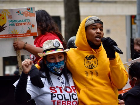 A speaker addresses the marchers, demanding immigration reform, equitable vaccine access, cancelling rent debt and evictions, and solidarity against police brutality, white supremacy, and systemic racism.