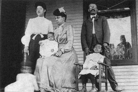 An old black and white image (circa 1904) of a Black mother, father, and four children — three young and one adolescent — pose for a picture on their front porch. The seated mother in a long dress and hat of the era holds her infant on her lap.