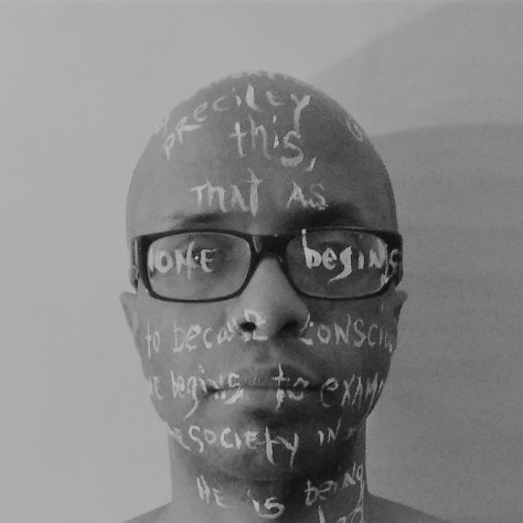 Tyrone Brown photographed with James Baldwin quotes painted on his face.