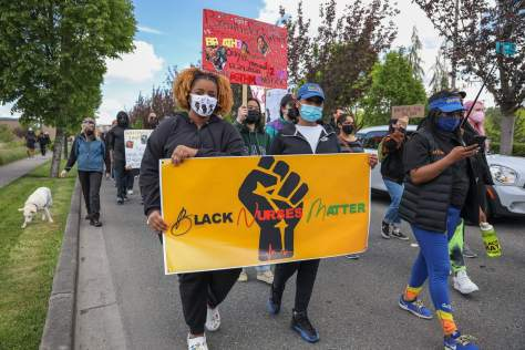 """Marchers carry a sign yellow sign with a black fist that reads """"Black Nurses Matter."""""""