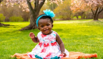 A Black-presenting toddler sits on an orange blanket in a green field with blossom trees in the background wearing a bright-blue headband and bright pastel-colored dress.