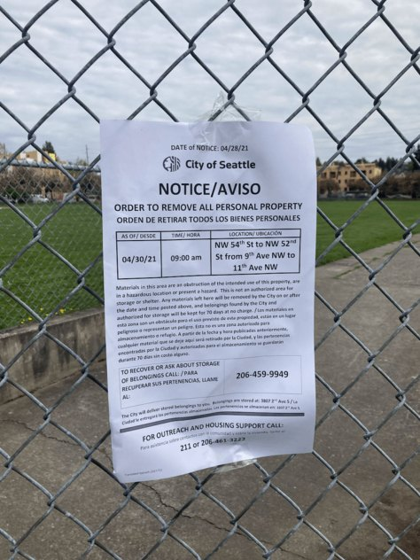 A Seattle Parks Department notice posted to a chain-link fence.