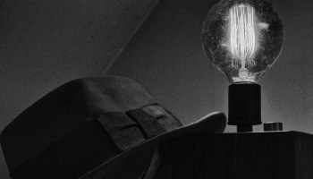 Black-and-white photo of a fedora hat leaning against an old-fashioned light with an edison bulb.