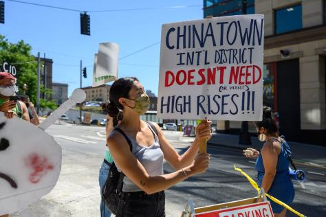 Summer Petitt holds an anti-displacement sign at a protest of the grand opening of KODA condos in the CID, February 25, 2021. The demonstration was organized by the CID Coalition (aka Humbows Not Hotels), Parisol (Pacific Rim Solidarity Network), and MPOP (Massage Parlor Outreach Project).