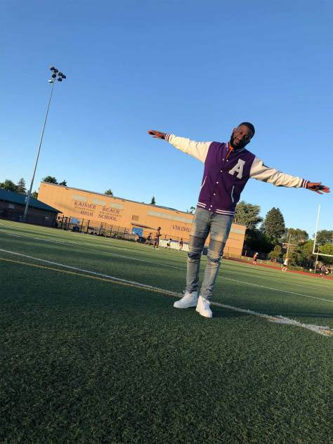 Drew Campbell on the field where his football career began, wearing his ACE Academy jacket.