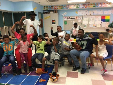 Drew Campbell as an instructional assistant in an Access Class at Leschi Elementary, with classroom visitor (and mentor) former Seahawk Jordan Babineaux.