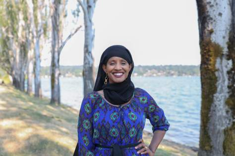 Photo of Shukri Olow standing in front of a tree-lined body of water.