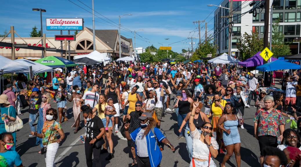Photo of hundreds of people dancing the Electric Slide on a city street in Seattle.