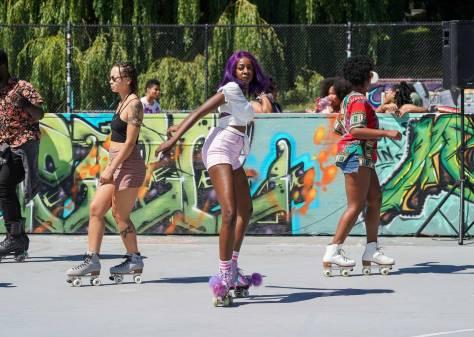 Black female-presenting individuals roller skate around Judkins Park for Black Girls Roller Skate's Juneteenth roller skating party.