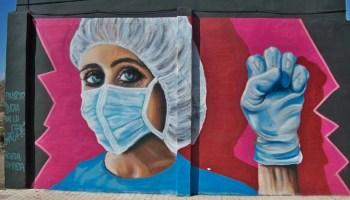 photo of mural of nurse in scrubs wearing mask, fist raised
