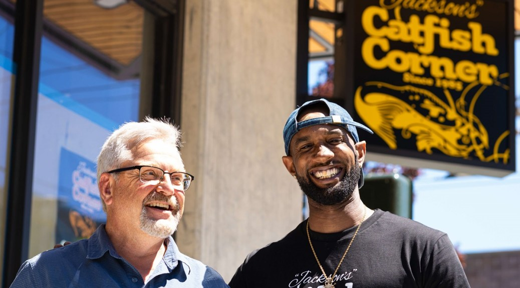 photo of Chris Szala (left) , Executive Director at Community House Mental Health Agency, and Jackson's Catfish Corner Owner Terrell Jackson (right) stand in front of his new restaurant location at the Patricia K Apartments development. Their grand opening will be on Juneteenth