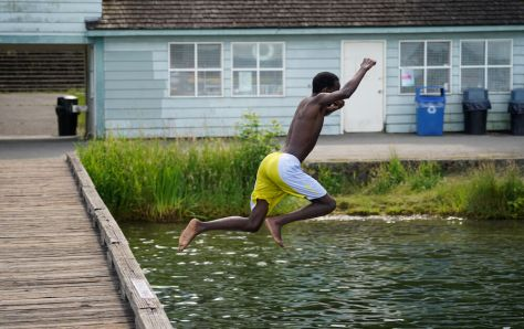 A teenager leaps into Lake Washington to escape the record breaking heat. (Photo: Susan Fried)