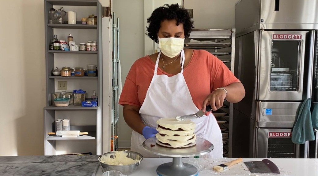 Hana Yohannes frosting one of her cakes.