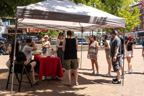 Event attendees line up in front of the Chinatown-International District Business Improvement Area tent to learn more about food deals restaurants were having during the day.
