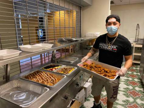 Jeremy Thunderbird carries Native Soul's catered dishes and prepares to serve them.
