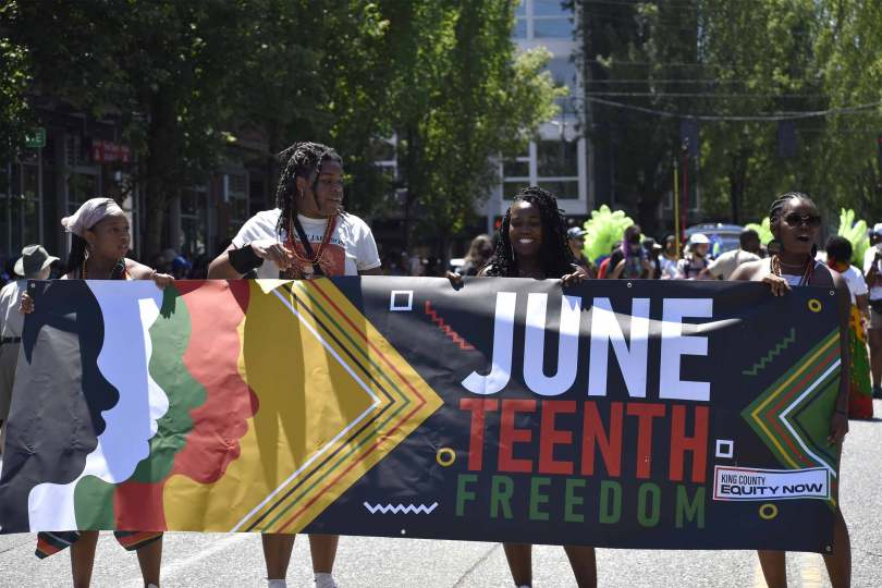 Black youth hold the banner at the start of King County Equity Now's Juneteenth Freedom March.