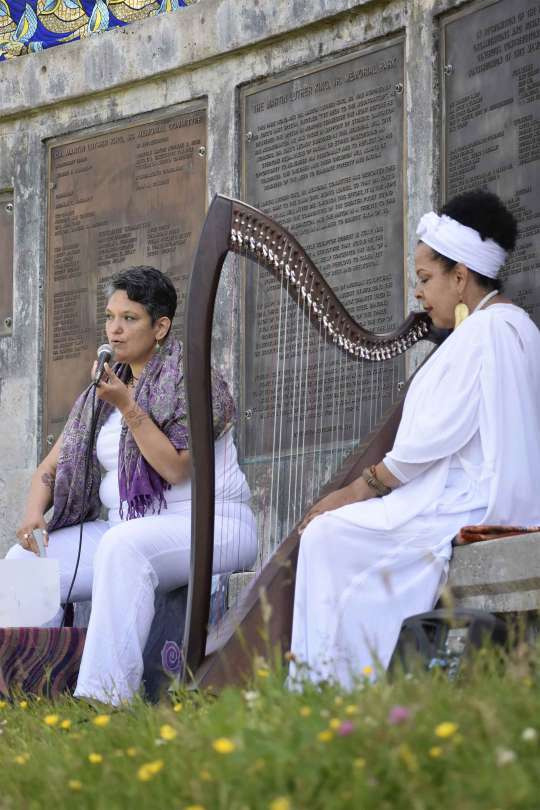 Two female-presenting individuals sit in MLK Jr. Memorial Park wearing white and speaking into a microphone. One of the individuals is seated before a harp.